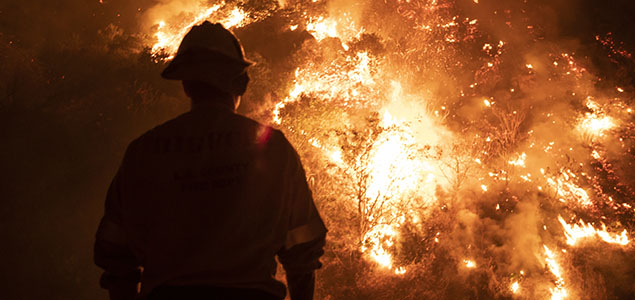 Firefighter standing in front of blazing wildfire